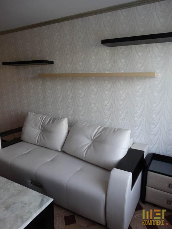 кожаный диван и полки на стене